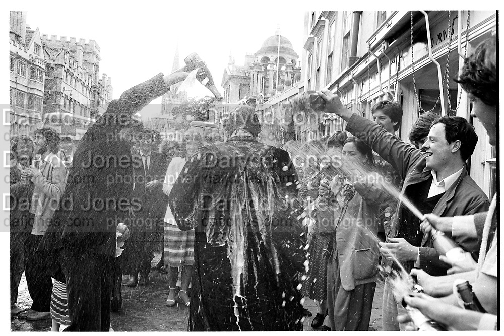 Champagne Spraying after finals. Oxford High St. Oxford 1981. SUPPLIED FOR ONE-TIME USE ONLY> DO NOT ARCHIVE. © Copyright Photograph by Dafydd Jones 248 Clapham Rd.  London SW90PZ Tel 020 7820 0771 www.dafjones.com