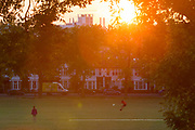 During the UK's Coronavirus lockdown, the May Bank Holiday brought warm temperatures for Londoners who stayed late in their local green space and as the sun sets over residential roofs, a person throws a frisbee in Ruskin Park, in Lambeth, on 24th May 2020, in London, England.