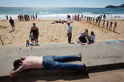 Manly beach. Weekend swimming test for children. Man having a nap.