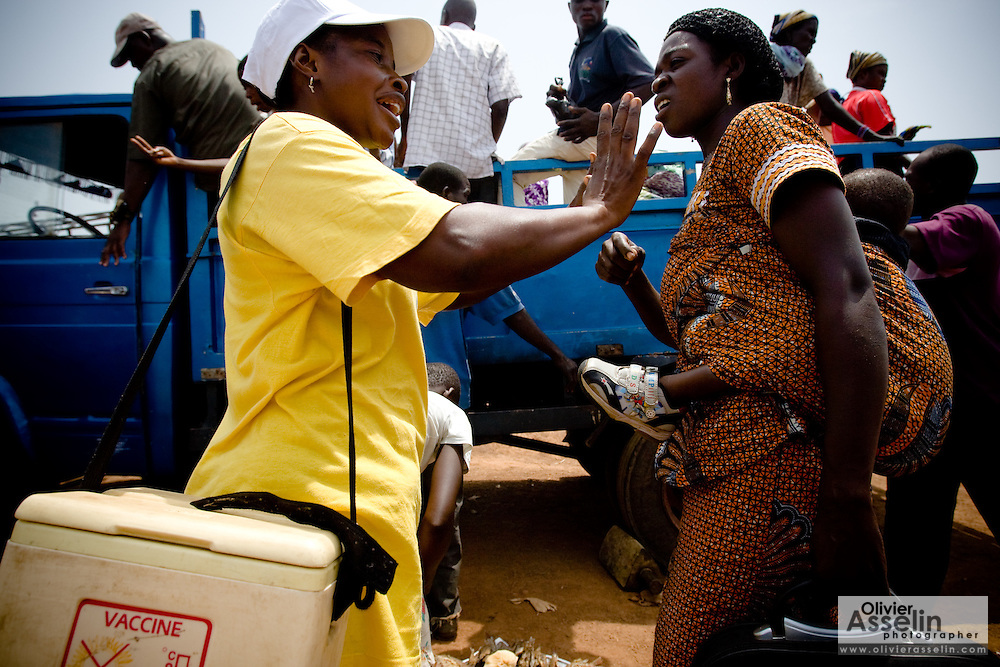 A health worker speaks to a woman  during a national polio immunization exercise in the town of Makango, northern Ghana on Thursday March 26, 2009.