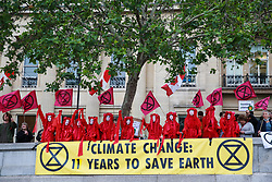 London, UK. 11 June, 2019. The Blood of the Extinction theatrical group join fellow activists from Extinction Rebellion in disrupting the Royal Opera House BP Big Screen's Romeo and Juliet event in Trafalgar Square in protest against oil sponsorship of the arts. Activists at the 'Petroleo and Fueliet' protest highlighted the contradiction between the Government and Greater London Authority having declared a climate emergency and BP being given a platform to sponsor the Royal Opera House event in the heart of London.