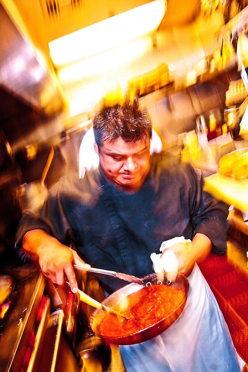 Geraldo Perez, cousin of executive Chef Martin Perez, prepares osso bucco with saffron risotto milanese, in the kitchen of Miami Beach's Osteria del Teatro.