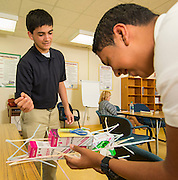 Seniors Moses Navarro, left, and Osmar Barrera work on the load tolerance of their straw bridge during in a summer intern program with FH-HP at Washington High School, June 16, 2014.