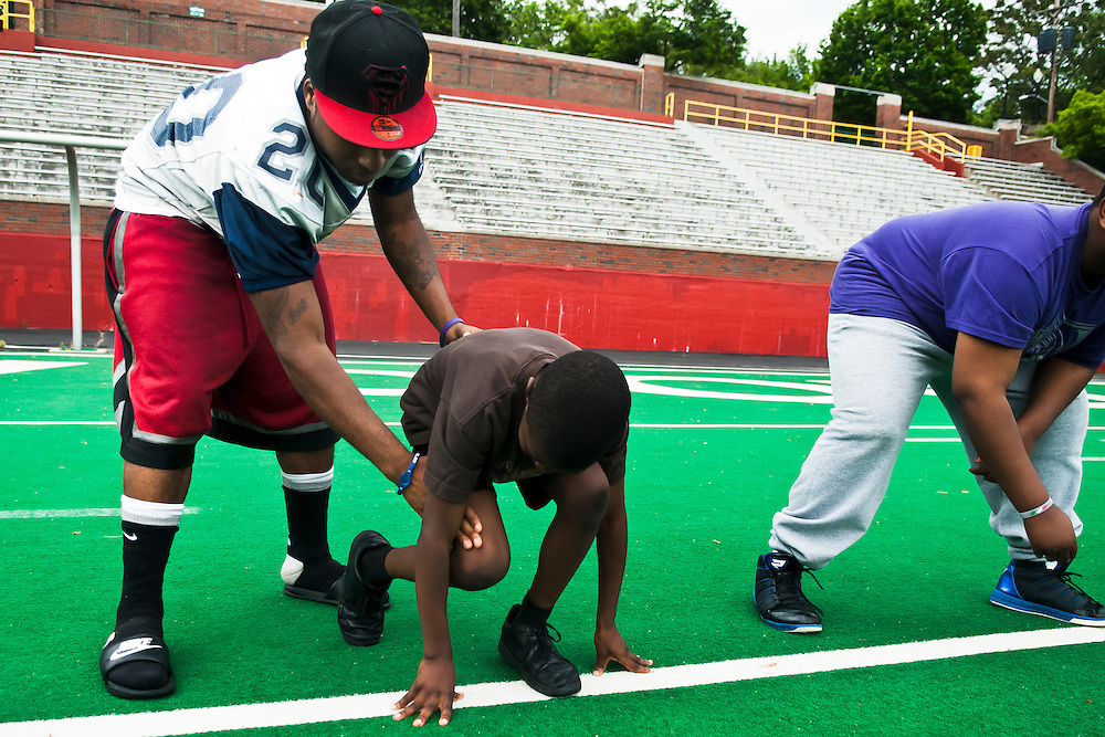 Lathan Goumas | MLive.com..Flint Fury running back Charvez Stewart shoes Montae Terry, 9, of Flint, how to get into a two point stance during a youth football camp at Atwood Stadium in Flint, Mich. on Saturday May 26, 2012. The team hosted a single day camp free for area youth.