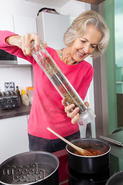 Senior woman cooking food using pepper grinder