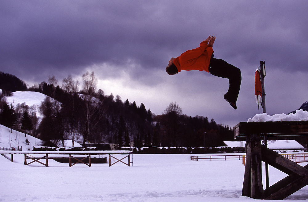A man performs a backflip from a jetty onto a snow covered lake