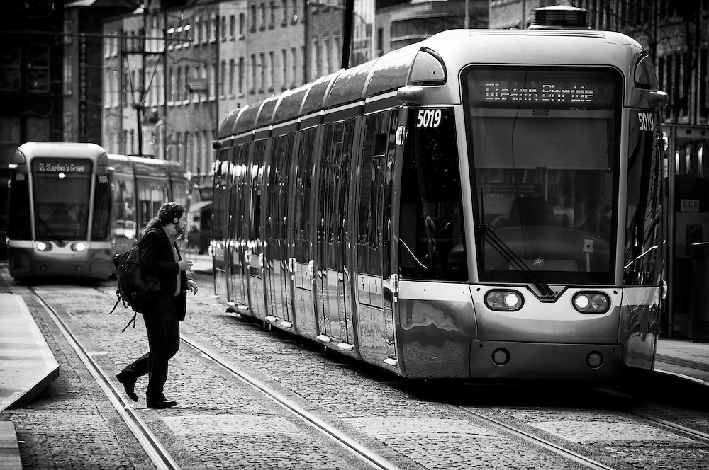 Stephen's Green, Dublin, Ireland: A man crosses in front of the busy Luas tram line as a tram comes to a halt at the stop