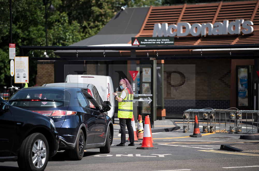 © Licensed to London News Pictures. 20/05/2020. Staines, UK. A MacDonalds employee hands out leaflets to customers as they queue at a McDonalds Drive Thru in Staines, Surrey. Branches of McDonalds restaurants have opened for drive thru today for the fist time since lockdown.  todayGovernment has announced a series of measures to slowly ease lockdown, which was introduced to fight the spread of the COVID-19 strain of coronavirus. Photo credit: Ben Cawthra/LNP