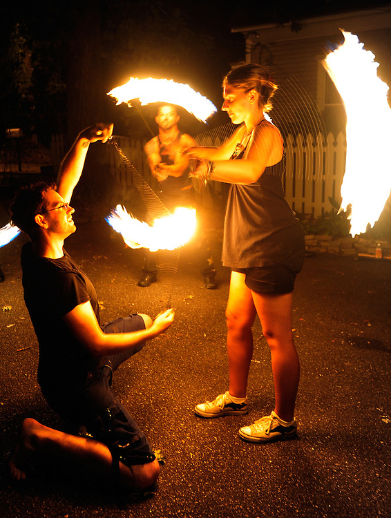 Vince Walzberg, left, and Charly Byram, right, perform a dual stunt with spinning orbs of fire while Mark Aaron Osl works with his staff during a get together or poi spinners at Walzberg's home on Saturday, Sept. 4, 2010 in Athens, Ga..