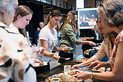 """A patron tries a sample dish during the """"Garver Gourmet"""" hosted by Sitka Salmon Shares at the newly opened Garver Feed Mill event space in Madison, Wisconsin, Saturday, Sept. 7, 2019."""