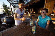 Phu Quoc Island. Ong Lang Beach. Mango Bay Resort. Waitress serving sundowners at the restaurant.