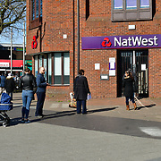 Coronavirus threat - People queue outside NatWest Bank only allow one at a time to entry bank, on 23 March in Walthamstow, London, UK.