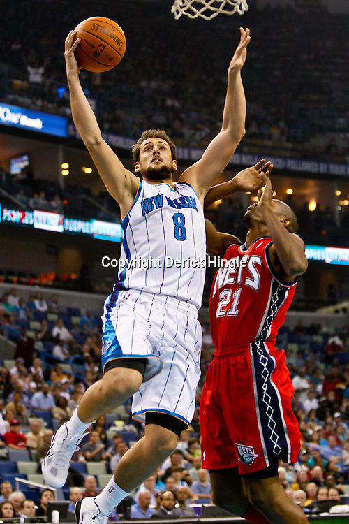 December 22, 2010; New Orleans, LA, USA; New Orleans Hornets shooting guard Marco Belinelli (8) shoots over New Jersey Nets small forward Travis Outlaw (21) during the first quarter at the New Orleans Arena.  Mandatory Credit: Derick E. Hingle