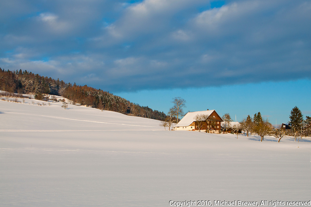 Beautiful Swiss winter landscape featuring a traditional Swiss farmhouse on a snow-covered hill against a blue sky.