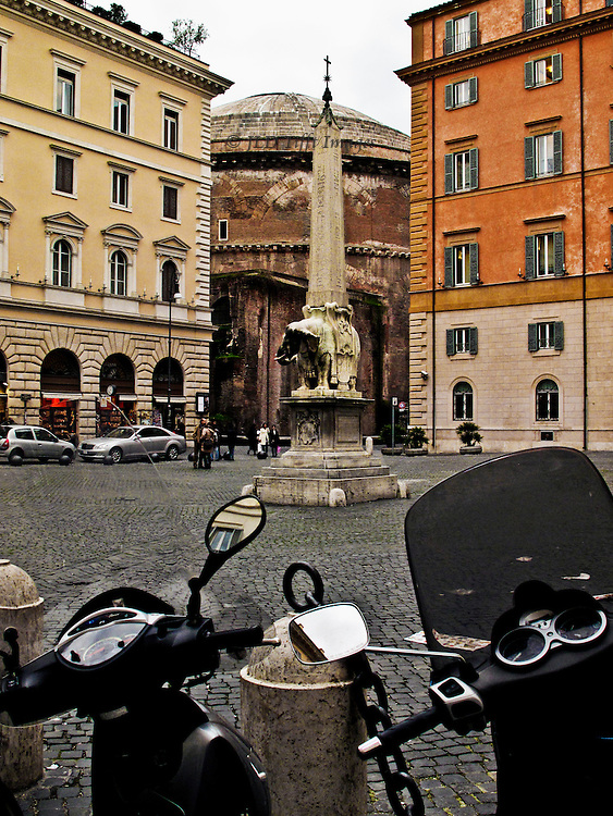 Piazza Sta Maria sopra Minerva, Bernini elephant and obelisk, Pantheon partially visible between two adjoining buildings beyond, motorbikes in foregound.  Casual juxtaposition of contemporary necessities of urban life in Rome with its still vital ancient structures and ornaments.