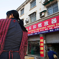 """Hunan, Liuyang, Dec. 19, 2013 : Mrs. Zhu. an employee that produces  firecracker lits ,unloads cardboxes at the """"Liuyang  interational firecrackers exhibition and trade city """" which is    a local wholesale market for the firecracker industry."""