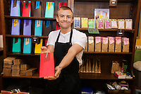 Portrait of male salesperson showing product in coffee store