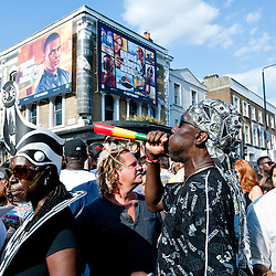 London, UK - 26 August 2013: a man plays a horn during the annual parade at the Notting Hill Carnival.