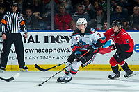 KELOWNA, BC - DECEMBER 30:  Nikita Krivokrasov #8 of the Prince George Cougars back checks Kaedan Korczak #6 of the Kelowna Rockets as he skates with the puck during first period at Prospera Place on December 30, 2019 in Kelowna, Canada. Korczak was selected in the 2019 NHL entry draft by the Vegas Golden Knights. (Photo by Marissa Baecker/Shoot the Breeze)
