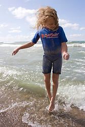 Little girl in a wetsuit jumping up out of the surf in Lake Michigan