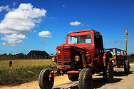 Red tractor with trailer on a country road in the tobacco farmland near San Luis, Pinar del Rio, Cuba.