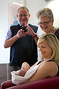Grand parents visiting their new born grand daughter in the midwife led birth centre, Chelsea and Westminster Hospital, London.