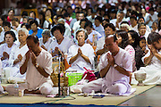 """22 JULY 2013 - PHRA PHUTTHABAT, THAILAND:  People in a chanting service during the Tak Bat Dok Mai at Wat Phra Phutthabat in Saraburi province of Thailand, Monday, July 22. Wat Phra Phutthabat is famous for the way it marks the beginning of Vassa, the three-month annual retreat observed by Theravada monks and nuns. The temple is highly revered in Thailand because it houses a footstep of the Buddha. On the first day of Vassa (or Buddhist Lent) people come to the temple to """"make merit"""" and present the monks there with dancing lady ginger flowers, which only bloom in the weeks leading up Vassa. They also present monks with candles and wash their feet. During Vassa, monks and nuns remain inside monasteries and temple grounds, devoting their time to intensive meditation and study. Laypeople support the monastic sangha by bringing food, candles and other offerings to temples. Laypeople also often observe Vassa by giving up something, such as smoking or eating meat. For this reason, westerners sometimes call Vassa the """"Buddhist Lent.""""     PHOTO BY JACK KURTZ"""