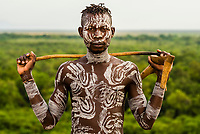 Kara tribe man with elaborate chalk painting on his body, Dus village, Omo Valley, Ethiopia.