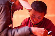 An instructor helps a young monk take an exam at the Shree Mahakaruna Sakyapa School in lo Manthang, Upper Mustang, Nepal.