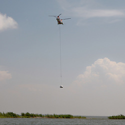 A helicopter drops 2,000 pound bags of sand into place, the bags dropped along the shoreline are used to prevent oil from reaching further into marshlands by creating a barrier off the coast west of Venice, Louisiana, U.S., on Tuesday, June 15, 2010.  Oil from Deepwater Horizon spill continues to impact areas across the coast of gulf states. (Mandatory Credit: Derick E. Hingle).