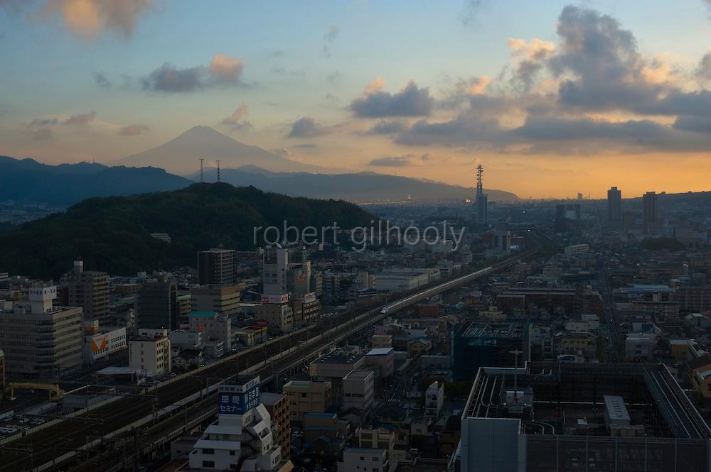 Mount Fuji is visible in silhouette as a bullet trains heads toward Shizuoka Station  in Shizuoka City, Shizuoka Prefecture Japan on 02 Oct. 2012.  Photographer: Robert Gilhooly