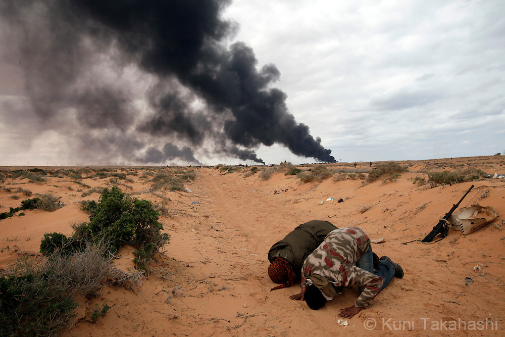 Rebel soldiers against Col. Muammar Gaddafi pray at frontline near Ras Lanuf on March 9, 2011. The government military and rebels kept fighting for taking control of the town for the last two days. .Photo by Kuni Takahashi
