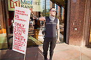 14 OCTOBER 2011 - PHOENIX, AZ:   A protester pickets Mid First Bank in Phoenix while Occupy Phoenix march past the bank in Phoenix, AZ. About 300 people participated in the Occupy Phoenix march through downtown Phoenix Friday evening, Oct. 14. The march was the first event in the Occupy Phoenix protests which start with the occupation of Cesar Chavez Plaza, a large square in downtown Phoenix.  PHOTO BY JACK KURTZ