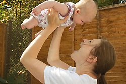 Mother lifting baby in the air. (This photo has clearance for the mother to be depicted as having mental health issues including post natal depression.)