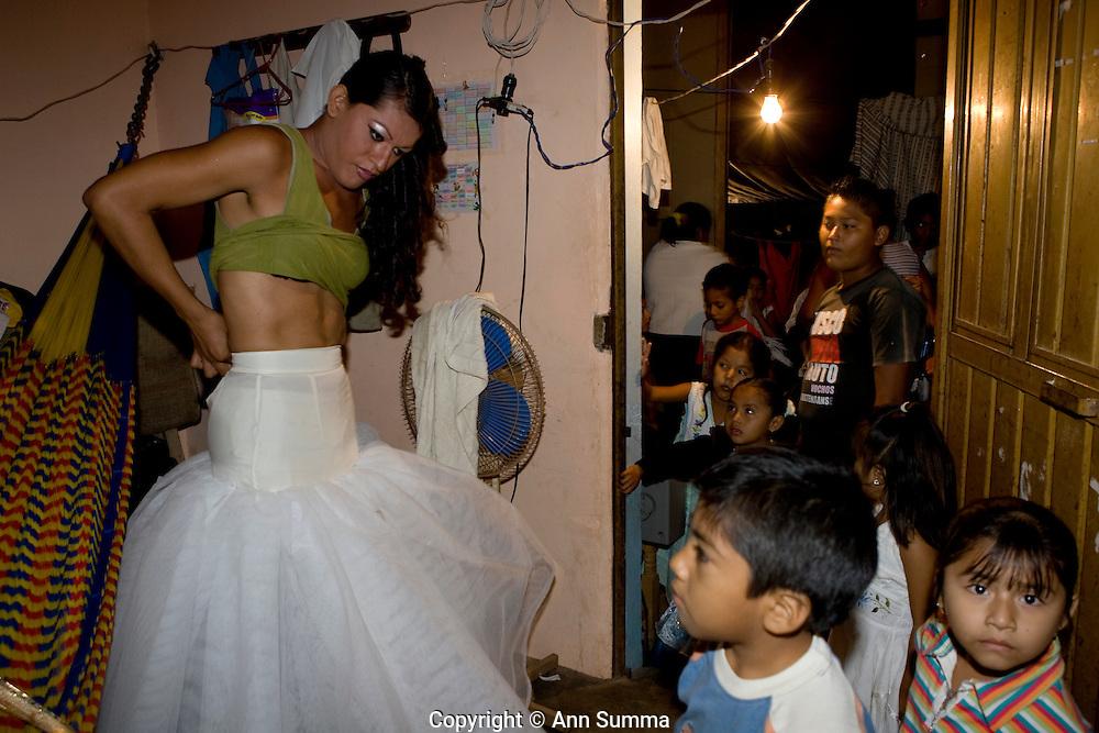 "Juchitan, Oaxaca: Queen of the ""Baila conmigo"" muxe (transvestite) vela (party), Julissa (Eojelio Teran Hernandez) gets dressed while family watches, at home in the 5th ward of Juchitan, Mexico. (Photo: Ann Summa)."