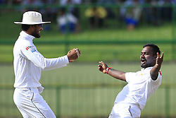 August 12, 2017 - Colombo, Sri Lanka - Sri Lankan cricketer Malinda Pushpakumara celebrates the dismissal of Indian batsman Ajinkya Rahane(unseen) with Sri Lankan cricket captain Dinesh Chandimal(L) during the 1st Day's play in the 3rd Test match between Sri Lanka and India at the Pallekele International cricket stadium, Kandy, Sri Lanka on Saturday 12 August 2017. (Credit Image: © Tharaka Basnayaka/NurPhoto via ZUMA Press)