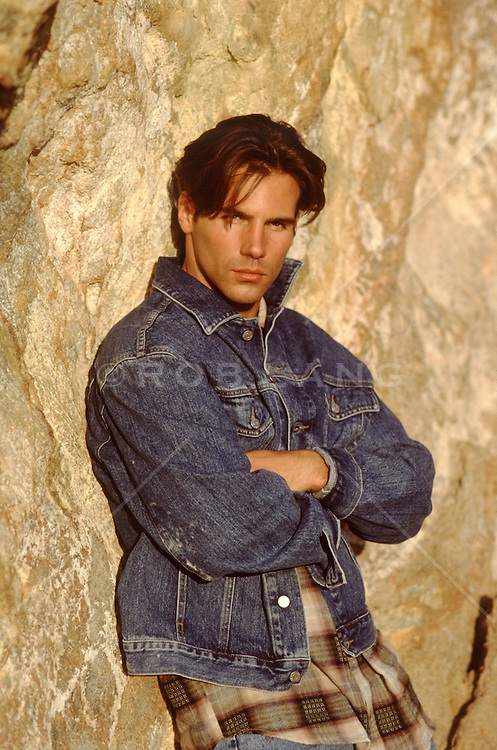 sexy handsome man leaning against a rock formation
