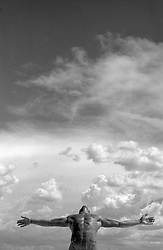 nude muscular man leaning back against the cloud covered sky