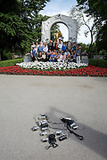 Tourist group from China taking souvenir pictures with the Johann Strauss statue at the Stadtpark.