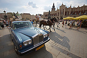 Poland, Krakow. Rynek Glówny (Market Square). Town Hall Tower and Cloth Hall. Rolls Royce and horse carriage..