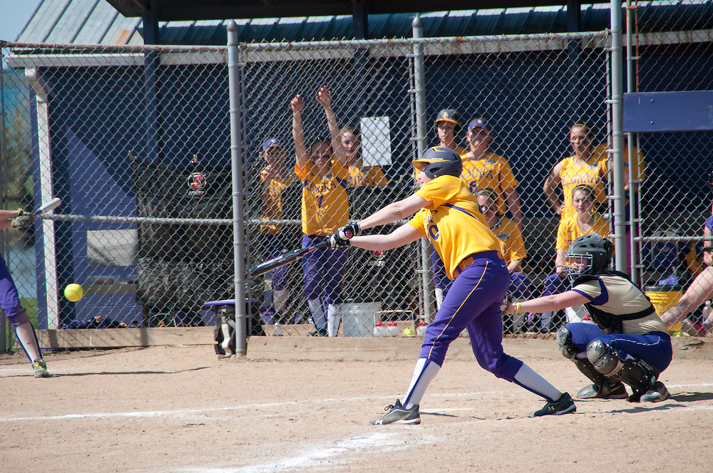 Elmira college batter reaches out to hit the ball during a softball game.