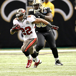 December 16, 2012; New Orleans, LA, USA; Tampa Bay Buccaneers running back Doug Martin (22) runs as New Orleans Saints defensive tackle Sedrick Ellis (98) pursues during the third quarter of a game at the Mercedes-Benz Superdome. The Saints defeated the Buccaneers 41-0. Mandatory Credit: Derick E. Hingle-USA TODAY Sports