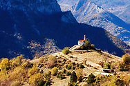 Small white church with a red roof and bell tower in the mountain