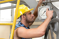 Side view of young male worker checking pressure gauge in industry