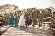 Bridal party walking over a bridge with sunset behind them