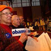 "2/10/08 -- BRUNSWICK, Maine. Georgiana Peacher of Brunswick  holds up an ""Obama for Me"" bumper sticker at her Democratic Caucus on Sunday afternoon. 1326 people voted (with their feet) at the Brunswick Middle School in the middle of a whiteout snowstorm. In Brunswick, Sen. Barack Obama (Dem-Ill) finished with 48 delegates and Sen. Hillary Clinton (Dem-NY) took 19. In Bath, Topsham and Harpswell and in the state as a whole, Obama also won. In the state race, Obama finished with nearly 1800 delegates to Clinton's nearly 1200. Photo by Roger S. Duncan. ..Bath:.Clinton 9,  Obama 17. .Harpswell.Clinton 6,  Obama 11..Topsham.Clinton 10,  Obama 15. .Brunswick :.Clinton 19,  Obama 48"