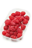 Fresh raspberries in a container against white background