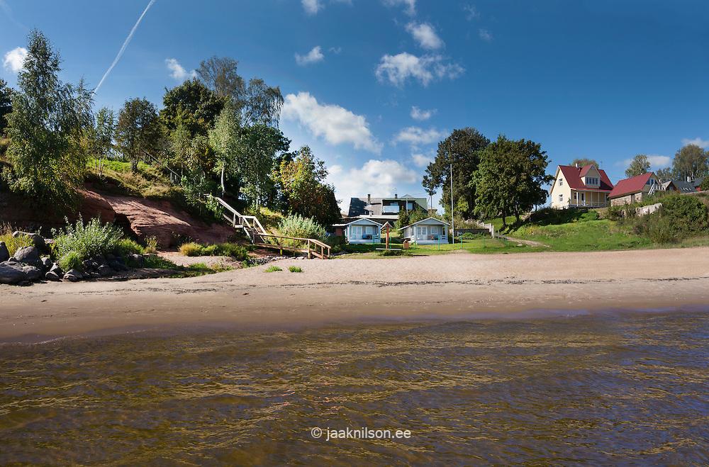 Red Kallaste sandstone outcrop at lake Peipsi in Estonia. Water, buildings at beach.