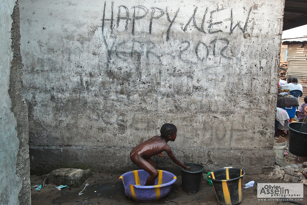 A girl bathes in a plastic container in the West Point slum in Monrovia, Montserrado county, Liberia on Monday April 2, 2012.
