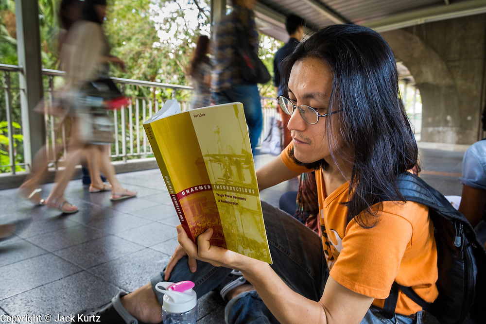 "31 MAY 2014 - BANGKOK, THAILAND: A man sits in the Skywalk between the BTS Skytrain Siam and Chit Lom stations to silently read George Orwell's ""1984"" and other books about civil disobedience and nonviolent protest. The protests are based on the ""Standing Man"" protests that started in Turkey last summer. Authorities made no effort to stop the protest or interfere with the people who were reading. Bangkok was mostly quiet Saturday. There were only a few isolated protests against the coup and military government.    PHOTO BY JACK KURTZ"